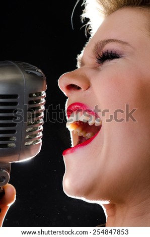Closeup portrait of female rock singer singing loudly into silver elvis-type microphone