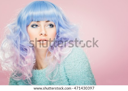 Closeup portrait of gorgeous young woman's face. Female model with pastel blue and pink hair, wearing turquoise sweater, posing against pastel pink background. Copy space, retouched.