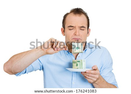 Closeup portrait of greedy, evil young ceo man in blue shirt eating green cash dollars from plate, isolated on white background. Negative emotion, facial expression feelings. Financial avarice concept