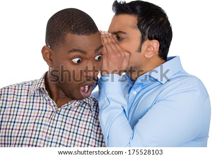 Closeup portrait of guy whispering into man's ear telling him something secret and disturbing. Shocked surprised disbelief wide open mouth response. Negative human emotions facial expression feelings