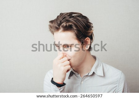 Closeup portrait of handsome guy, businessman closing nose, something stinks. Negative human face expressions, emotions, feelings, reaction, attitude, behavior, perception