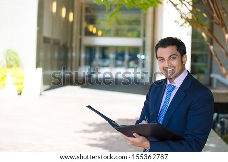 Closeup portrait of handsome young smiling businessman in suit reviewing some documents, standing outside of his company building, on a sunny day, isolated on a city urban background. Corporate life.