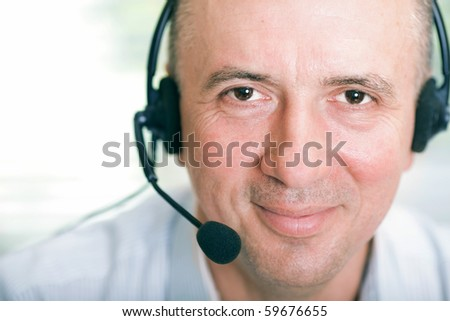 Closeup portrait of happy mature business man with headset