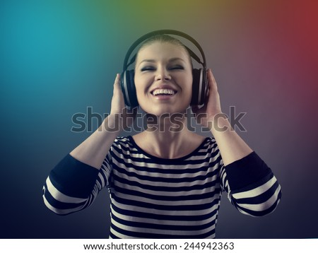 Closeup portrait of party girl in earphones. Pretty smiling Caucasian woman listening music, relaxing in night club.