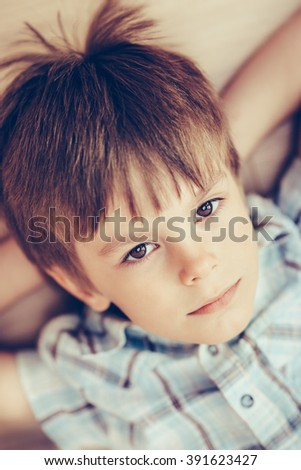 Closeup portrait of pensive little boy with brown eyes wearing checkered shirt lying on floor and looking at camera. Happy childhood concept, selective focus on eyes, top view, instagram filters