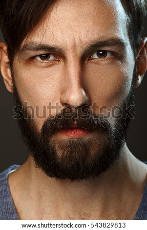 Closeup portrait of serious man with beard and mustache looking straight severe severe.