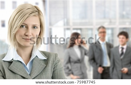 Closeup portrait of smiling businesswoman with coworkers in background.?