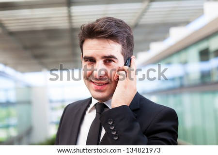 Closeup portrait of smiling young business man using cell phone at the office