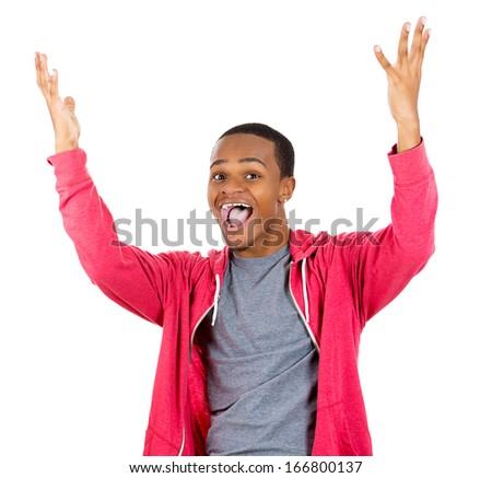 Closeup portrait of super happy excited smiling young man in red hoody with hands up in air, isolated on white background. Positive emotion facial expression feeling