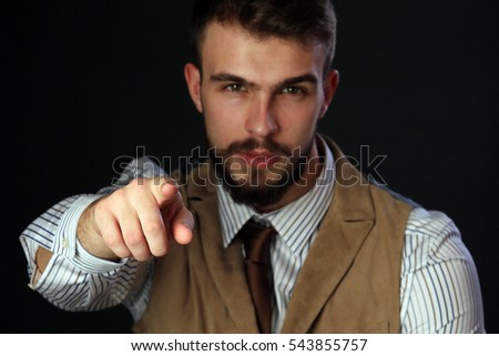 closeup portrait of the beautiful charismatic young man with a beard, It shows a finger at the camera on a dark background studio