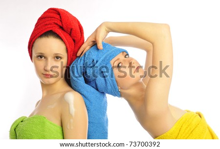 Closeup portrait of two beautiful young women after shower with towel on their heads standing together. Isolated on white background.