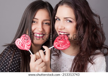 Closeup portrait of two young girlfriend girls with lollipops. Happy and cheerful teens. Red lips and hearts. Valentine's day concept.