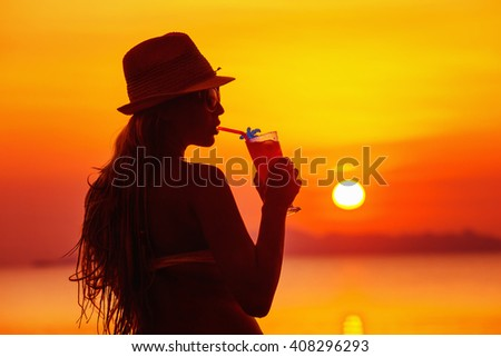 Closeup portrait of woman in hat with cocktail at tropical red sunset background.