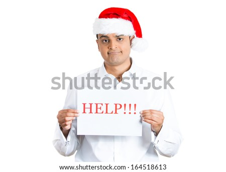 Closeup portrait of worried young man in red santa claus hat holding a help !! sign with hands, isolated on white background with space to left. Human emotion facial expression
