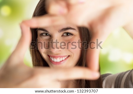 Closeup portrait of young beautiful woman making frame with her hands