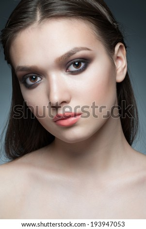 Closeup portrait of young beautiful woman with stylish smoky eyes makeup
