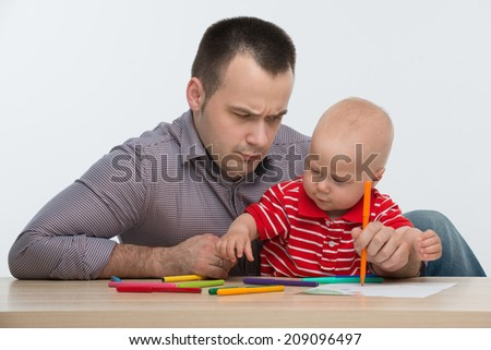 Closeup portrait of young handsome Caucasian father drawing with his cute toddler son, dad is confused, isolated on white