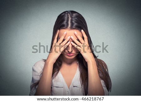 Closeup portrait sad young beautiful woman with worried stressed face expression covering face with hands looking down