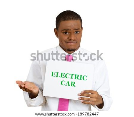 Closeup portrait, young, confused business man with pink tie holding sign which says electric car, green font, trying to make decision is it worth it isolated white background. Efficient dynamics