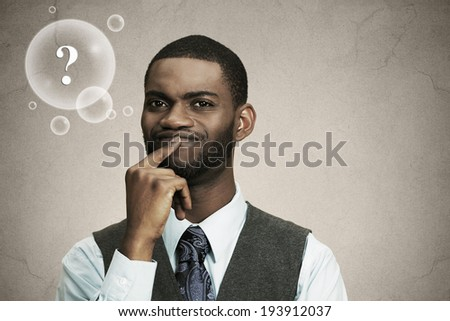Closeup portrait young, puzzled business man thinking, deciding deeply about something finger on lips looking confused isolated black background with question bubble. Emotion facial expression feeling
