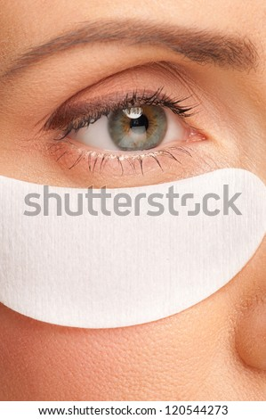 Closeup shot of beautiful woman applying gel eye mask. Middle Aged, beauty treatment