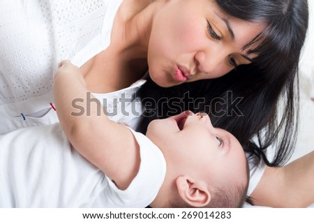closeup shot of beautiful young mom staring at her small cute baby