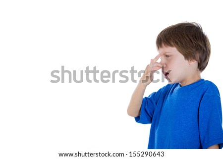 Closeup side view profile portrait of kid pinching and holding nose because something stinks, isolated on white background with copy space