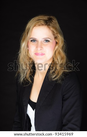 Closeup studio portrait of pretty young woman with pink lipstick and long blond hair. Wearing a black suit. Isolated on black background.