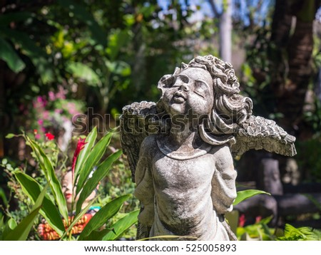 Closeup vintage beautiful charm cement angle statue in the garden on blurred background.