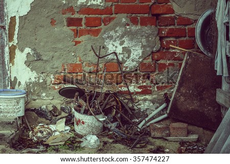 Closeup, vintage. The collapse of the plaster with brick wall of an old rural house. Old broken utensils, junk, trash.
