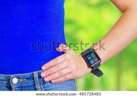 Closeup waist young sporty female wearing blue top with bare arms, smart watch on arm, screen lit up, green forest background