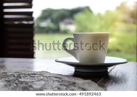 Closeup white cup of coffee on wooden table with nature background
