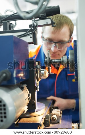 Closeup worker in uniform and protective glasses working on sharpening machine tool
