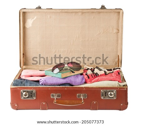 Clothes and book, glasses on old suitcase isolated on white