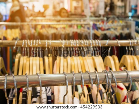 Clothes hang on rack shelf in clothing store