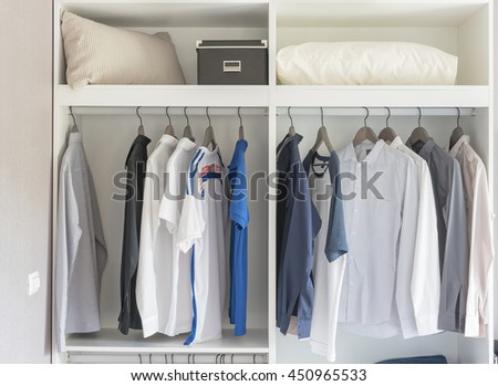 clothes hanging in white closet with white pillows and box