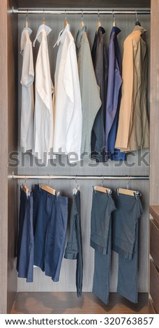 clothes hanging on rail in wooden wardrobe at home