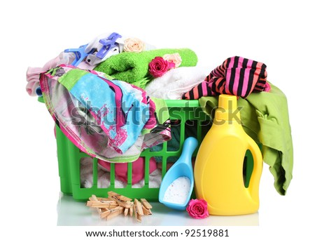 Clothes with detergent and washing powder in green plastic basket isolated on white