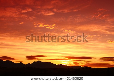 clouded orange sky with mountain silhouette
