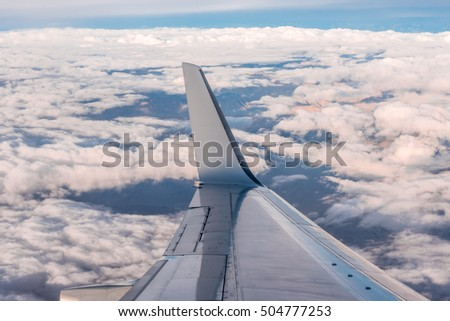 cloudy sky and airplane wing as seen through window on aircraft. Flying in the sky and the sea of clouds