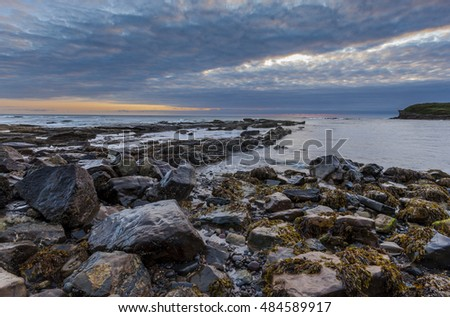 Cloudy sunrise over rocky beach at Colywell Bay, Seaton Sluice on the north east coast of England, UK.