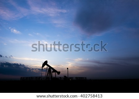 Cloudy sunset and silhouette of crude oil pump in the oilfield