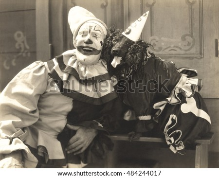 Clown posing with dog dressed in clown costume