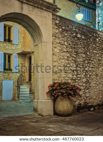 Cobbled street with flowers in the old village Tourrettes-sur-Loup at night, France.