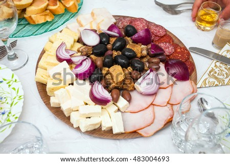 Cocktail food appetizer with ham, salami, red onions, pork chops and a variety of olives and cheeses