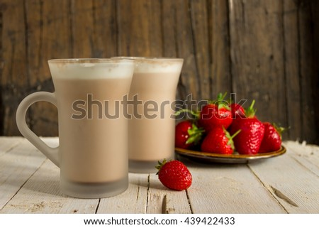 Cocoa with whipped cream and strawberries on a wooden background. Healthy eating