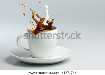 Coffee and milk splashing in white cup. Pouring milk into coffee.