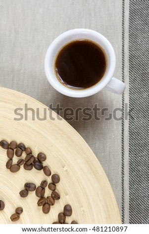 Coffee beans and coffee cup on wooden background. Top view.