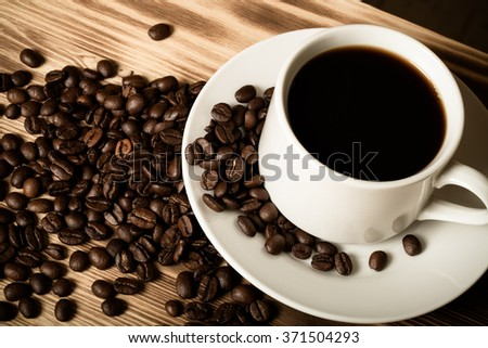 Coffee beans and coffee in white cup on wooden table for background. Toned.