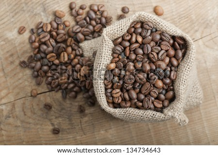 coffee beans in jute bag on wooden table
